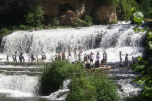People wading in the falls