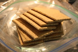 Preheat oven to 350 degrees (f).  Place 12 graham crackers into large zip top bag and crush to a powder.