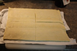 Defrost puff pastry per package directions and lay out in one flat sheet.  Divide into quarters with a very sharp knife to avoid damaging the layers of pastry dough.