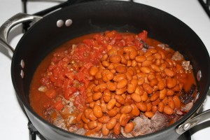 Pour the can of tomatoes and the can of beans into the skillet.