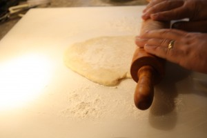 "Roll out the pizza dough with a rolling pin until it's 1/4"" thick."