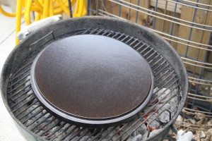 Pour your coals around the outside edge of your charcoal grill.  Place your upside down dutch oven lid in the center of your grill grate.  Cover to preheat.