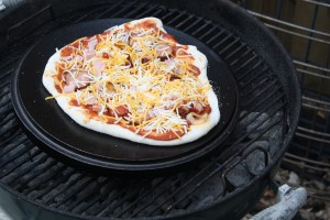 Pizza on a dutch oven lid over a charcoal fire.